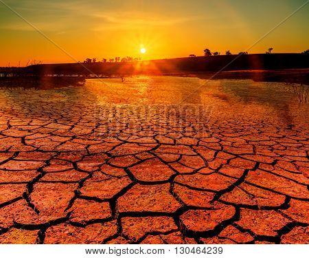 Global warming concept. hot sunset, drought cracked desert landscape