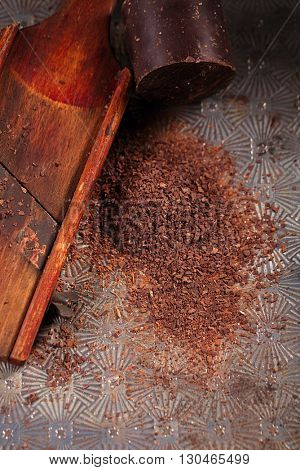 grated 100% dark chocolate flakes on vintage  wooden grate,   shallow DOF
