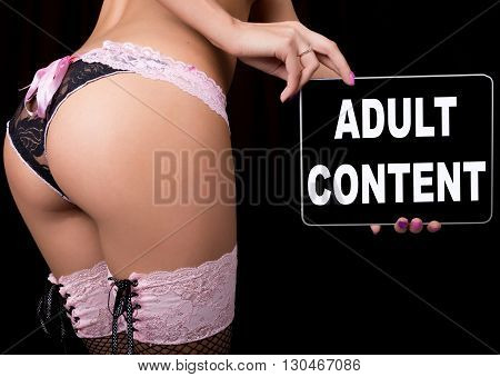technology, internet and networking - close-up ass of girl in lacy lingerie, holding a tablet pc with adults content sign. Adult content.