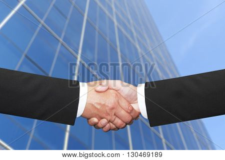 background of two businessmen shakehand with skyscraper background