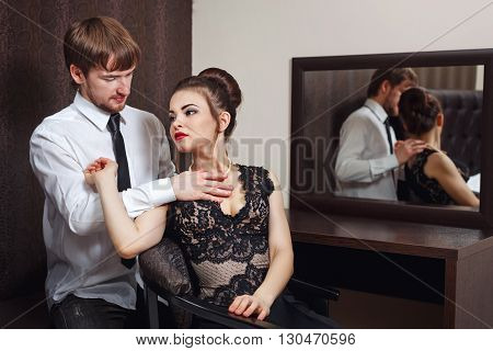 Married couple. Romantic evening at the hotel. Love and passion. Man corrects a necklace around the neck of his wife.