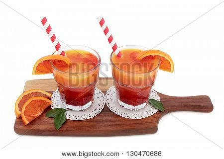 Blood orange fruit juice drink in glasses on doilies with striped straws on a maple wood board over white background. High in vitamins, anthocyanins and antioxidants.