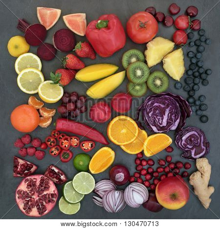 Large fresh fruit and vegetable selection on a slate background, high in antioxidants, anthocyanins, dietary fiber and vitamins.