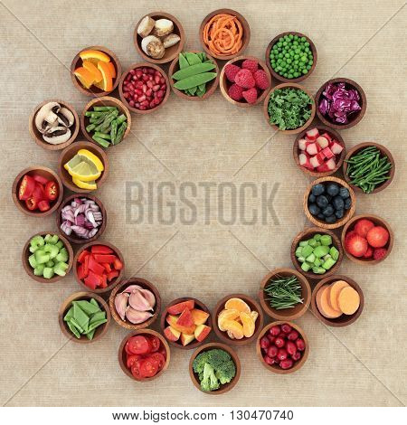 Health and super food selection of fresh fruit and vegetables in wooden bowls over brown grunge paper  background,. High in vitamins, antioxidants, minerals and anthocyanins.