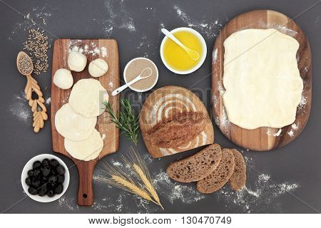 Rustic bread  loaf with baking ingredients of dough on maple boards, olive oil, yeast, herbs, wheat sheaths and rye grain in lovespoon with olives over grey.