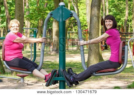 Elderly senior and young woman in sports wear exercising lower body on outdoor gym in sunny park trainer machine healthy sporty lifestyles and slimming concept