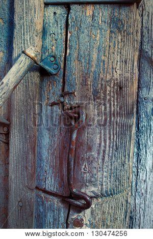 Fragment of a rural wooden door with a metal hook.