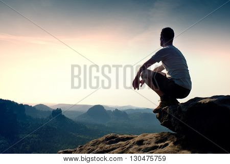 Young Man In Black Sports Pants And Grey Shirt  Is Sitting On Cliff's Edge And Looking To Misty Vall
