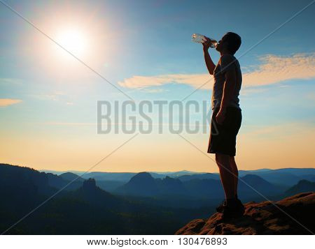 Thirsty Hiker In Black Pants Drinks From Bottle Of Water. Sweaty Tired Tourist On The Peak Of Sandst