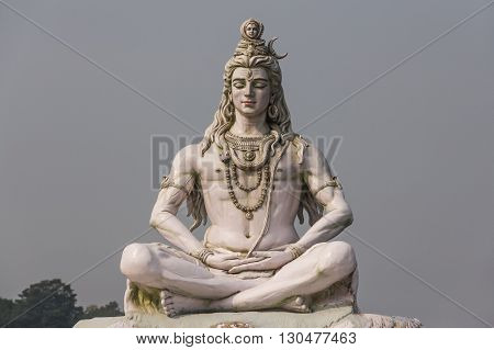 RISHIKESH INDIA - CIRCA NOVEMBER 2011 - the sculpture of Hindu god Shiva sitting in meditation on Ganges river embankment in front of Parmarth Niketan ashram