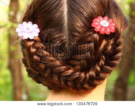 girl head back view with plait and hair clips on the summer green background teen pretty girl with long dark hair on the country background
