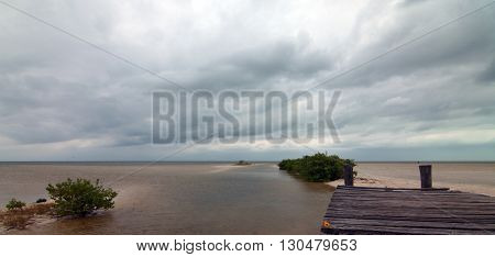 Abandoned Deteriorating Boat Dock in Isla Blanca Cancun Mexico under storm swept cloudscape