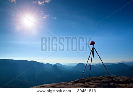 Tripod with red baseball cap on the peak ready for photography. Sharp autumn rocky peaks increased from gold foggy background.