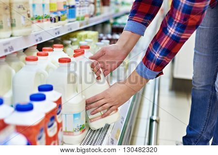 The woman shopping milk in grocery store