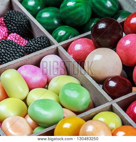 multi colored candy and chewing gum in a wooden box