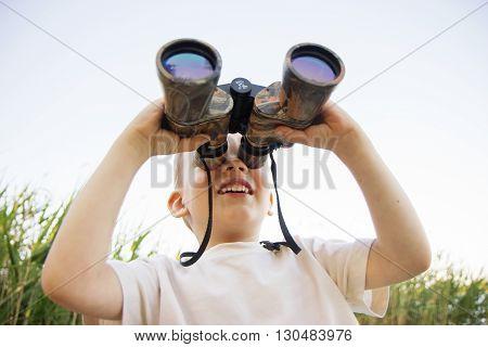 Little Boy Looking Through Binoculars On River Bank