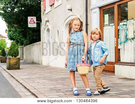 Portrait of fashion kids in a city, cute kids posing outdoors, adorable little girl and her brother wearing blue clothes
