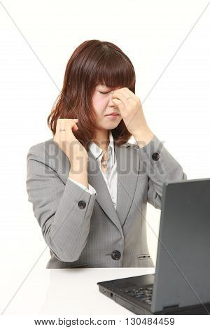 portrait of young Japanese businesswoman suffers from Asthenopia on white background