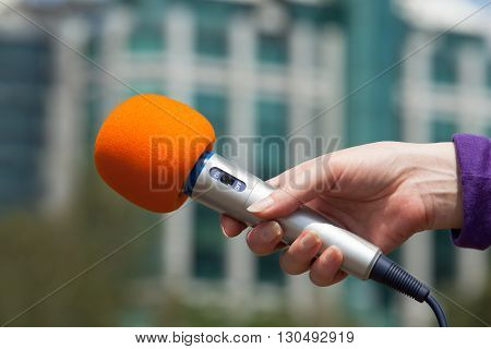 Press interview. Microphone in focus against blurred background.