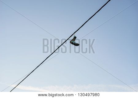 Old pair of sneakers dangling on power line cable against blue sky life change concept