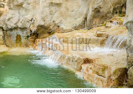 Close up of waterfall in outdoor pool at a resort.