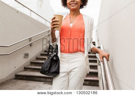 business, drinks, lifestyle and people concept - close up of young smiling african american businesswoman with coffee cup walking downstairs to city subway
