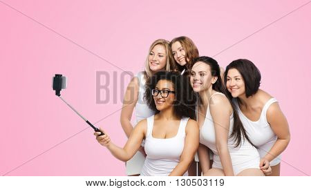 technology, friendship, body positive and people concept - group of happy women in white underwear taking picture with smartphoone on selfie stick over pink background