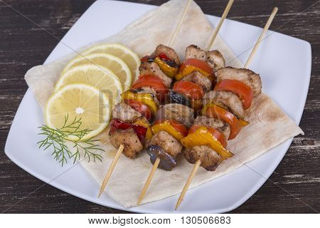 Grill chicken steak shish kabobs with vegetables in skewer on the plate