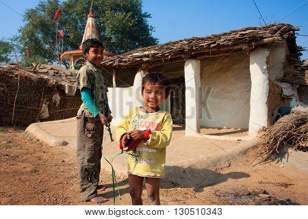 CHITRAKOOT, INDIA - DEC 29, 2012: Unidentified children play outdoor near the mud village houses on December 29, 2012 in Chitrakoott Madhya Pradesh India. Madhya Pradesh state has 105592 primary schools