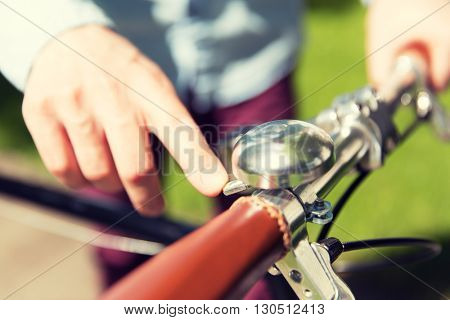 people, style, leisure and lifestyle - close up of male hand ringing retro ding dong bicycle bell on fixed gear bike wheel poster