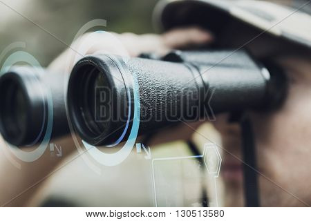 hunting, war, army and people concept - close up of young soldier looking to binocular with virtual hologram and observing forest