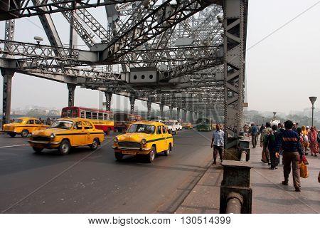 KOLKATA, INDIA - JAN 18, 2013: Yellow Ambassador taxi cabs goes on the Howrah bridge on January 18, 2013 in Kolkata India. Hindustan Ambassador is a car manufactured by Hindustan Motors of India since 1958