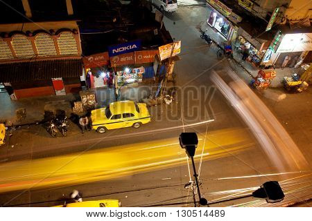 KOLKATA, INDIA - JAN 13, 2013: Night city with fast moving cars and Ambassador taxi cabs on January 13, 2013 in India. Hindustan Ambassador is a car manufact. by Hindustan Motors of India since 1958