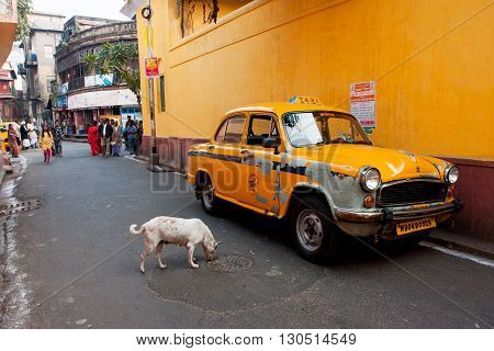 KOLKATA, INDIA - JAN 12, 2013: Antique yellow color taxi cab stoped on a narrow street with pedestrians on January 12, 2013 in India. The car is Hindustan Ambassador manufactured since 1958