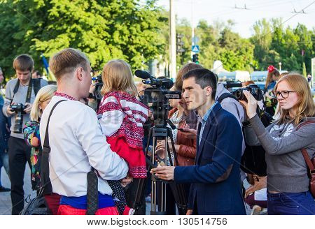 Zaporizhia/Ukraine- May 19, 2016: journalists interviewing man with a child dressed in traditional Ukrainian clothes on celebration of national Ukrainian embroidered clothes, known as Vyshyvanka  Day