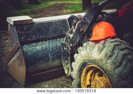 Construction Safety Helmet on Bulldozer Tire. Heavy Equipment Operation Safety.