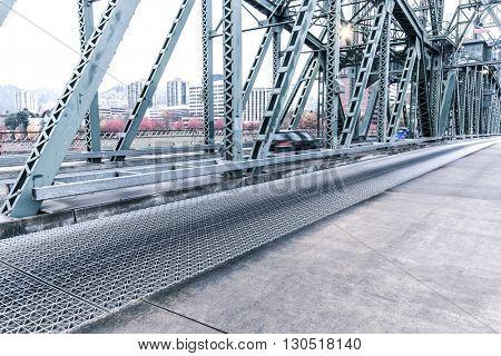 empty pedestrian walkway near road on steel bridge