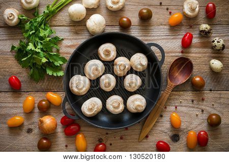 Mushrooms, tomatoes, parsley, spices and cooking utensils on wooden background. Top view, copy space. Mock up for recipe, cook book. Cooking background