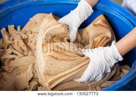 Baker's Hands Discarding Bread Waste In Garbage Bin
