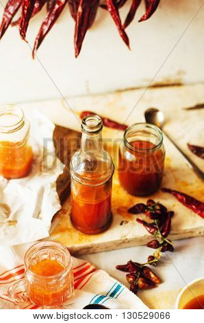 Red hot sweet chilli sauce over old white wooden background. Rustic styling. Pepper sauce with parsley and garlic in glass jar. Home made ketchup in a jar. Canning Marinara sauce