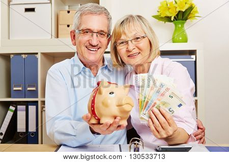 Smiling senior couple with euro money bills and a piggy bank