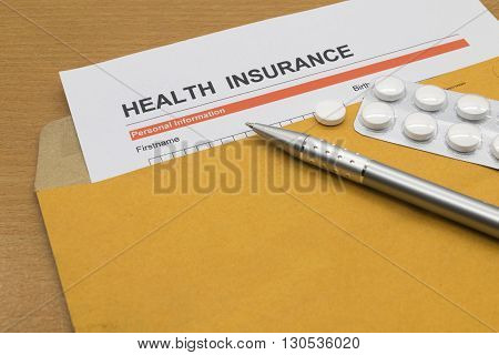 health insurance application form with sthetoscope and pen and medicine