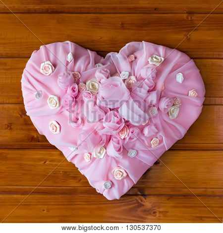 Pink Textile chiffon Heart with roses and other flowers on a wooden background.