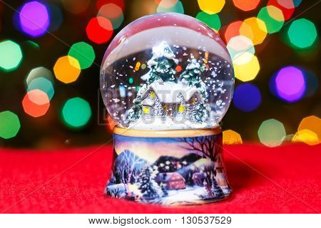 Christmas Snow Globe in front of Christmas tree lights closeup, blurred background