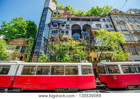 VIENNA, AUSTRIA - CIRCA APRIL 2016: Colorful apartment house   named Hundertwasserhaus with red tram in Vienna. This building is famous expressionist landmark designed by artist Friedensreich Hundertwasser