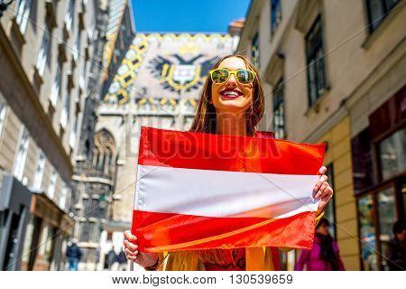 Young smiling woman holding austrian flag with the roof eagle emblem on the background in Vienna