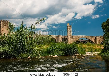 Ancient stone gothic bridge and river in the foreground