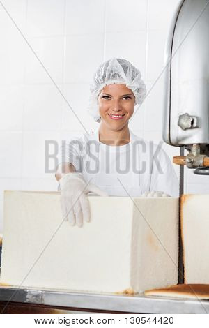 Female Baker With Bread Loaf Standing At Cutting Machine