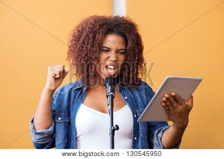 Woman Singing While Holding Tablet Computer