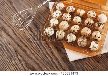 Quail eggs in a plastic box on a wooden background